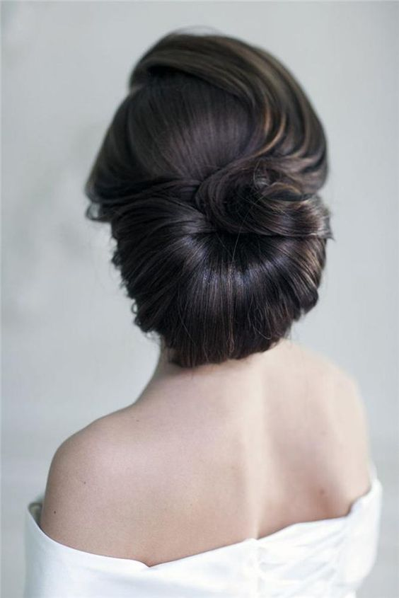 a unique retro inspired low updo with a curled top and a twisted lower part for a retro bride