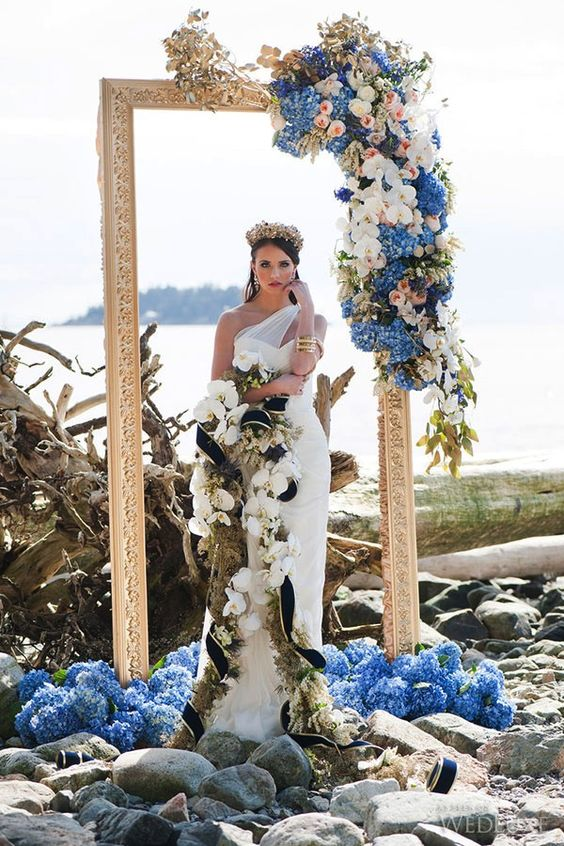 a unique wedding arch of a gold picture frame and super lush blue, pink and white blooms and gilded leaves