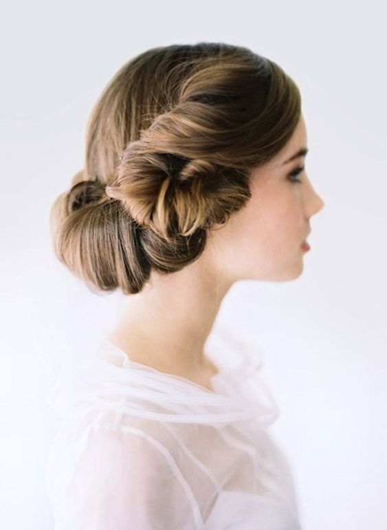 a unique wedding hairstyle with a twisted lower part and a sleek top is a fresh take on a vintage hairstyle