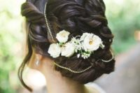 a vintage-inspired twisted and wavy updo with some locks down, beads and fresh flowers and greenery