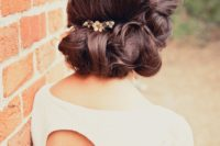 a vintage low updo with a twisted and wavy lower part and a volume on top plus a small hairpiece