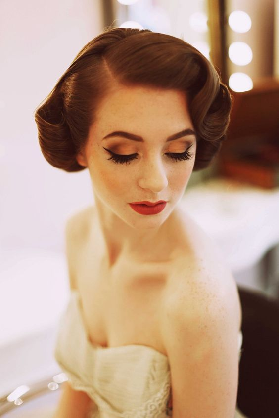 a vintage wedding updo with fixed curls on both sides and a sleek top