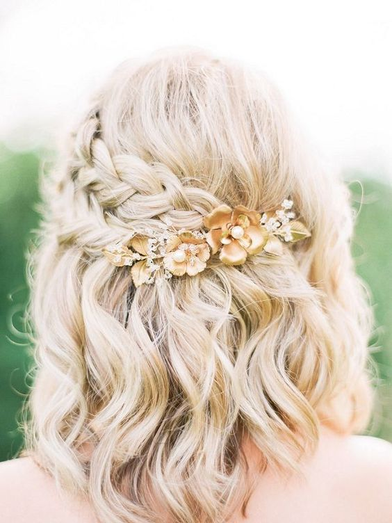 a wavy half updo with two side braids highlighted and secured with a floral hairpiece