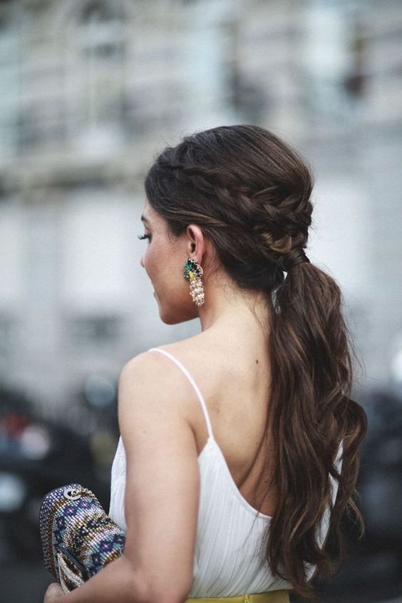 a wavy ponytail with a bump and a braided halo for a casual and modern bride