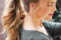 a wavy ponytail with a fishtail braid on one side and some bangs is a relaxed and casual wedding hairstyle idea