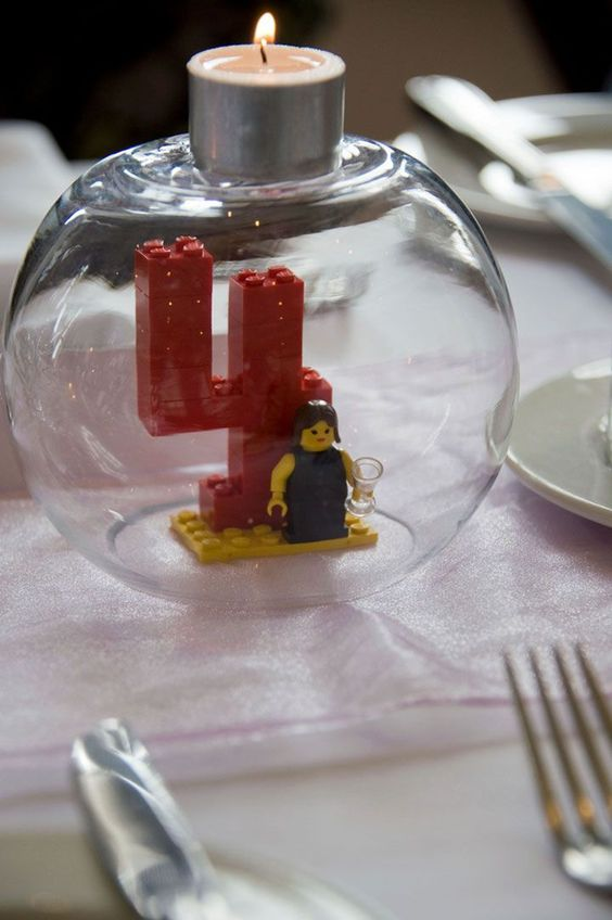 a wedding decoration of a bright Lego table number, a figurine and a tealight on top is a cool DIY