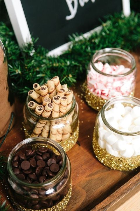 a wedding hot cocoa bar with jars with various sweets dipped in gold glitter look and feel like Christmas at once