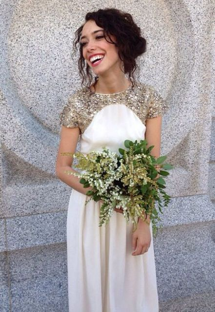 a white and gold glitter A-line wedding dress with short sleeves and a high neckline, a gold and green wedding bouquet for a lovely look