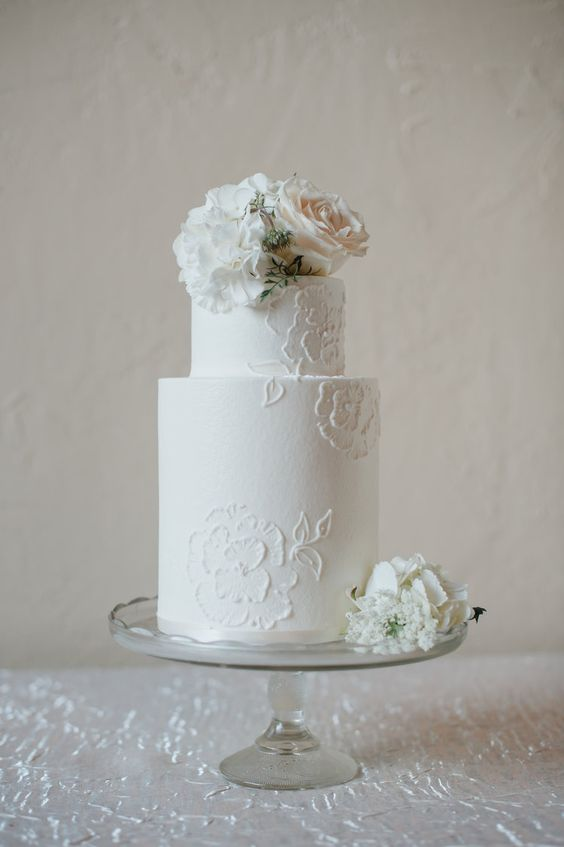 a white floral lace wedding cake with fresh blooms in blush and white is a timeless piece for any wedding