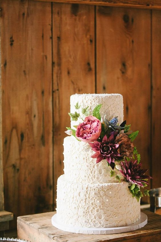 a white floral lace weddng cake decorated with burgundy and fuchsia plus bue fresh blooms for a more modern feel