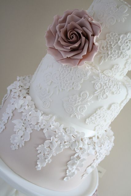 a white lace and floral wedding cake with a blush tier and a dusty pink sugar bloom is amazingly refined