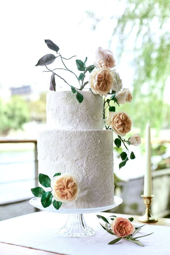 a white lace wedding cake topped with peachy blooms and some dark foliage that make it feel more modern and bold