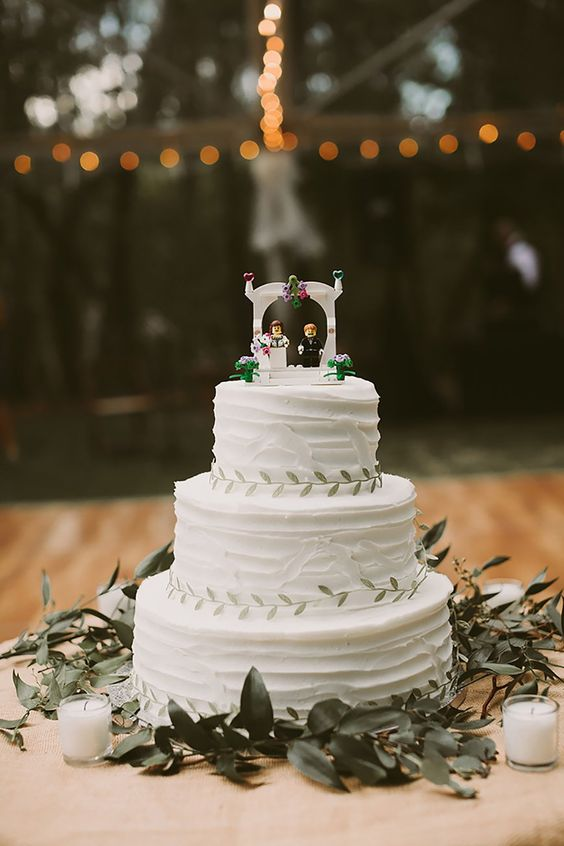 a white textural wedding cake with greenery and a creative wedding Lego cake toppers