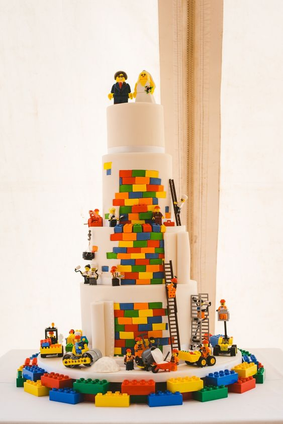 a white wedding cake with bright touches, lots of Lego figurines and cake toppers looks wow