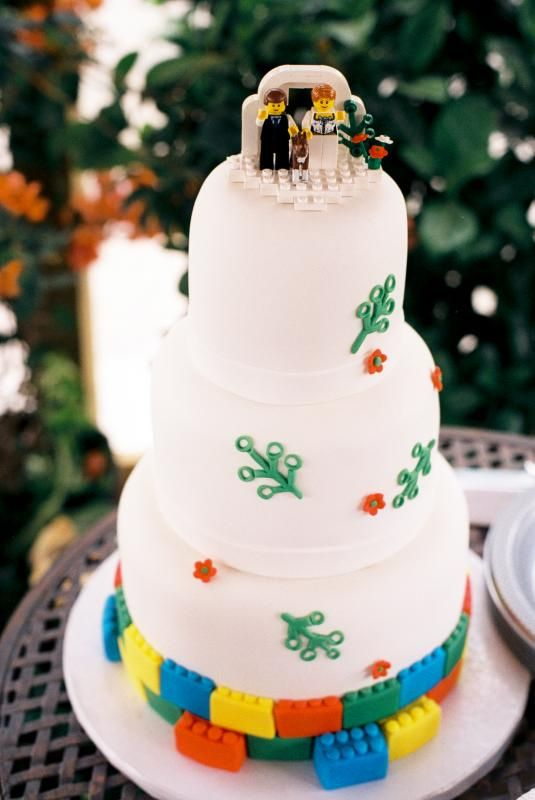 a white wedding cake with colorful Legos, bright touches and Lego figurines on top