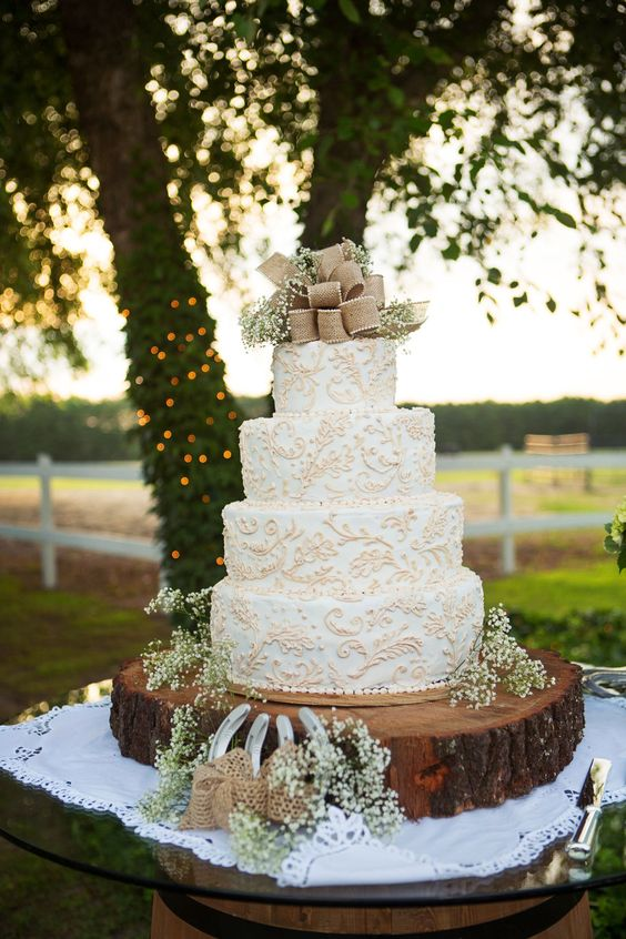 a white wedding cake with tan lace patterns, baby's breath and a burlap bow on top is great for a rustic wedding