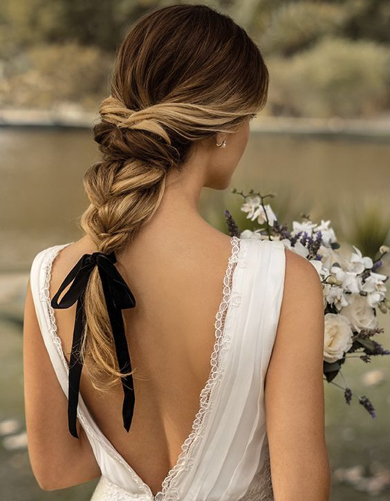 an elegant twisted braid with wavy ends and a black ribbon for an accent   it's a hot and trendy idea