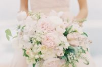 an oversized blush and cream asymmetrical bridal bouquet with some greenery