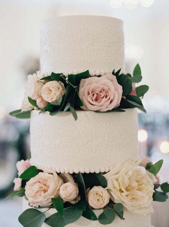 two white lace wedding cakes are highlighted with blush and neutral blooms in between