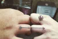 A romantic heart arrow wedding ring tattoos that is finishing on your partner's finger