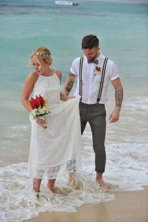 a beach groom's look with a white shirt, striped suspenders, grey pants and a bright boutonniere