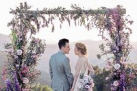 a beautiful lilac and purple wedding arch with greenery and various blooms