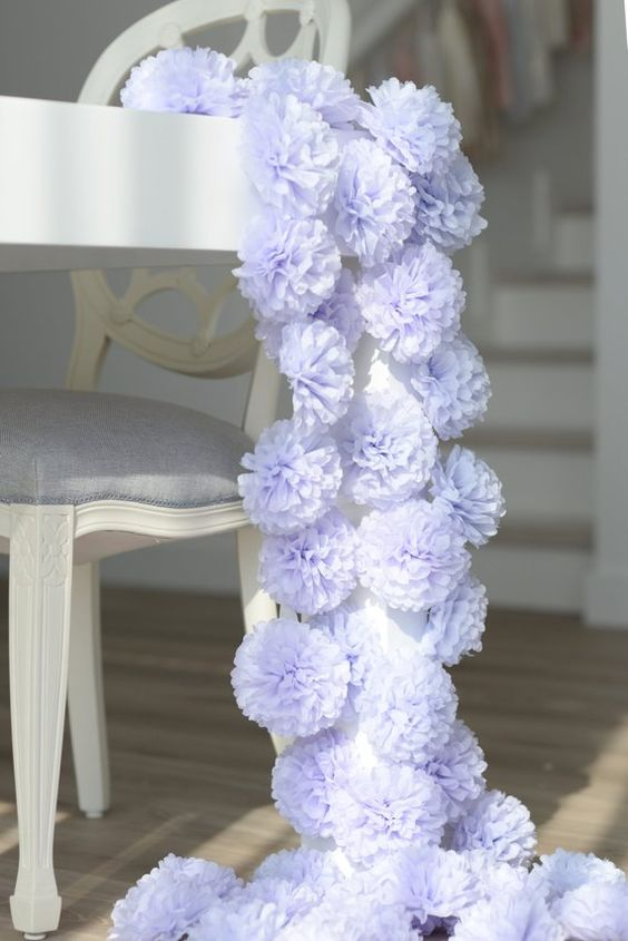 a blue paper pompom wedding table runner is a fun and budget-friendly idea for wedding decor