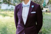 a bold groom's outfit with a purple blazer, a white shirt, a light blue bow tie and handkerchief, neutral pants