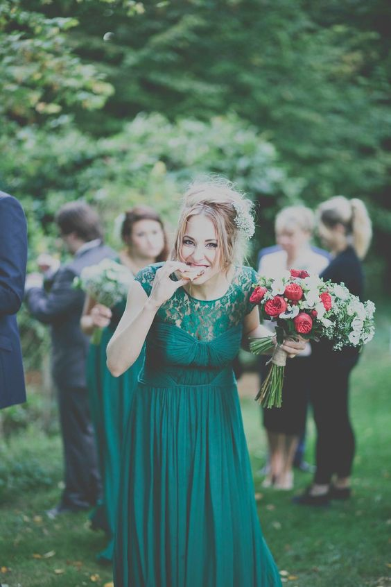 a bridesmaid dress in emerald with a faux strapless neckline, a lace bodice and a pleated skirt
