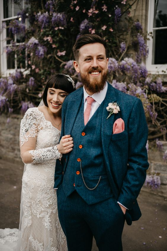 a bright blue tweed three-piece suit, a white shirt and a pink tie and handkerchief plus a chain and amber buttons
