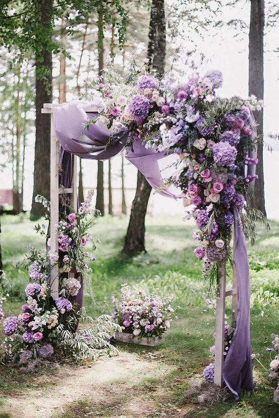 a bright lilac, purple and pink wedding arch with airy fabric for a romantic touch