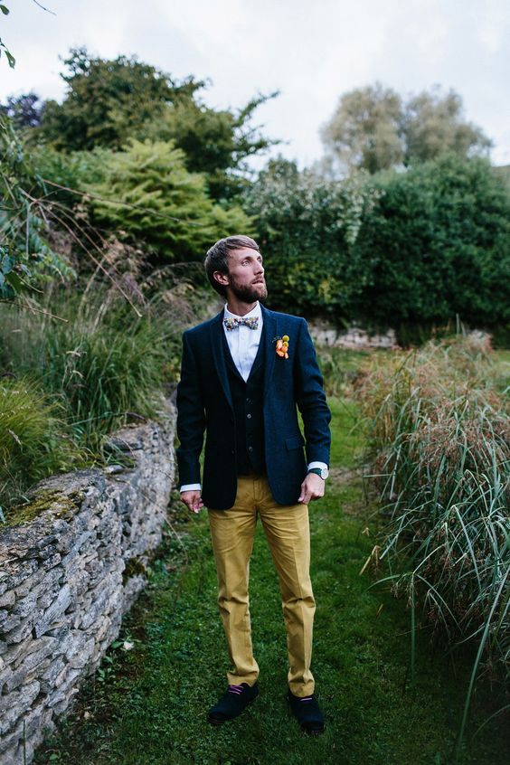 a bright outfit with mustard pants, a black waistcoat, a navy blazer, a colorful bow tie and navy shoes