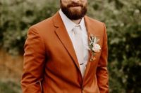 a bright rust-colored suit, a white shirt, a creamy tie and a florla boutonniere for a chic and stylish fall groom's look
