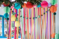 a bright wedding backdrop of colorful ribbons and colorful honeycomb pompoms is a fun idea for a festival wedding