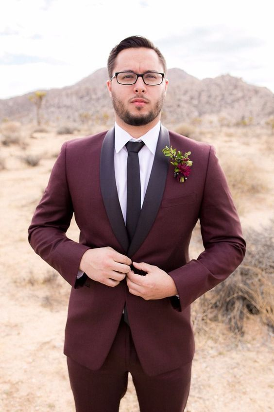 a burgundy tuxedo with black lapels, a white shirt and a black tie plus a bold floral boutonniere for a fall groom