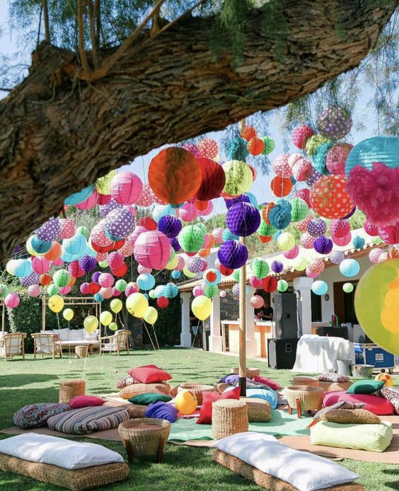 a colorful and fun fiesta wedding lounge with lots of bright balloons, paper pompoms and lanterns is all fun and joy