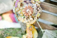 a colorful brooch wedding bouquet in all the bright colors with a long yellow silk wrap and ribbons