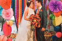 a colorful paper pompom and fan wedding arch and lots of blooms on the floor for a festival-themed wedding