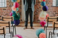 a colorful paper pompom and fan wedding arch with gold fringe is a very bold and cool idea to rock