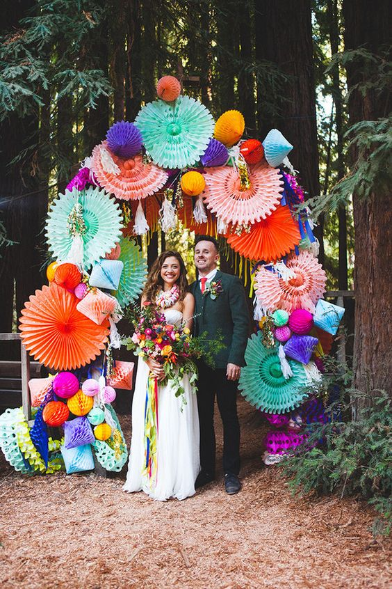 a colorful wedding arch covered with bright paper fans and honeycomb pompoms and rhombs is a fun idea