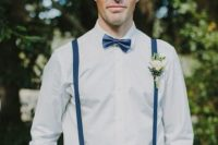 a creative and elegant groom's outfit with a white shirt, navy suspenders, a navy bow tie and pants