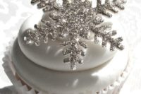 a cupcake with icing and a sparkly silver snowflake on top is perfect for a winter wedding