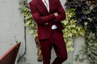 a deep red suit, a white shirt, black shoes with no socks for a bold and chic modern groom's look
