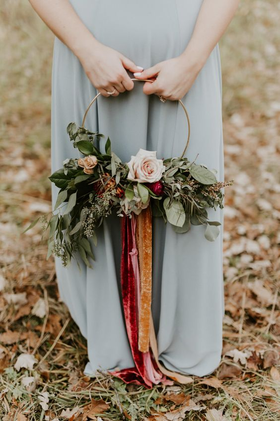 a floral hoop with colorful velvet ribbons that doubles as a non-traditional bouquet