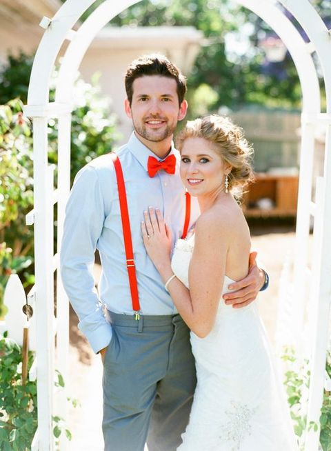 a fun summer groom's look with a blue shirt, red suspenders, a red bow tie and grey pants is outstanding