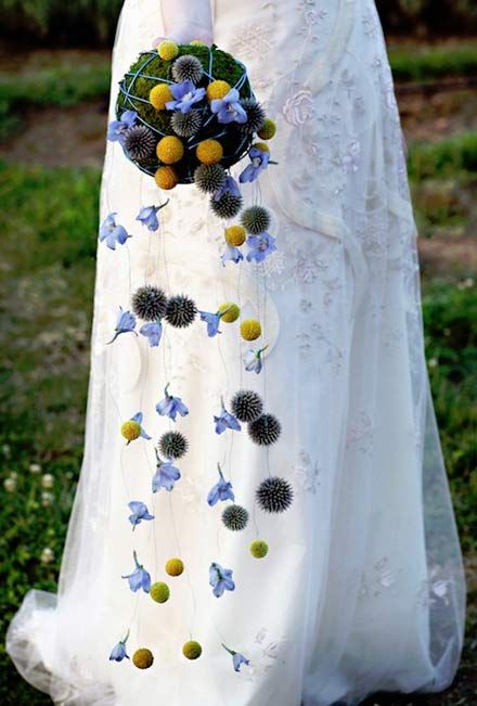 a funky wedding bouquet of a moss ball with blue blooms, billy balls and some blooms hanging down