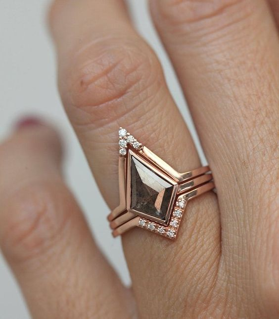 a geometric engagement ring with a kite shaped salt and pepper diamond and smaller ones on the edges is a beautiful idea