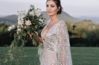 a gorgeous modern silver wedding dress with a nude underdress, wide sleeves and a plunging neckline and large sequins