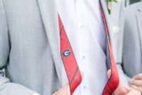 a grey suit, a white shirt, a printed bow tie, red striped suspenders and a greenery boutonnire