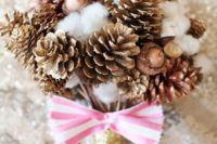 a holiday wedding bouquet with gilded pinecone,s cotton, acorns, a gold glitter wrap and a striped pink bow